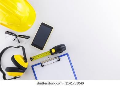 Construction safety wear and tools including hard day, goggles, earmuffs, tape measure, and clipboard plus a mobile phone on white background with copy space