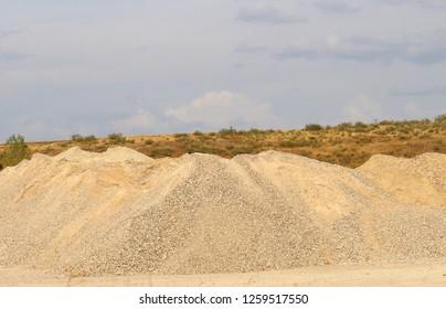 Construction sand. stack of sand. Pile of sand. gravel under blue sky.