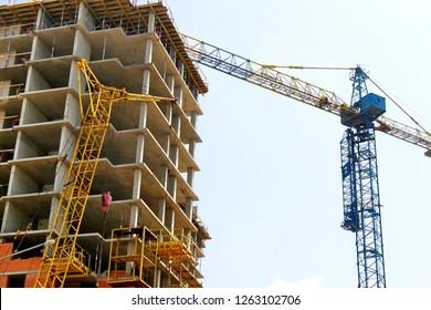 Construction site background. Concrete building under construction. Two cranes near the building.