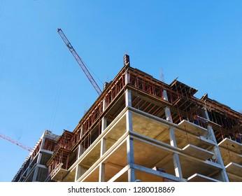 Construction site background. Concrete building under construction. Crane near building against blue sky.