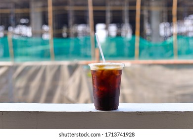 Construction site background with cup of ice blackcoffee.