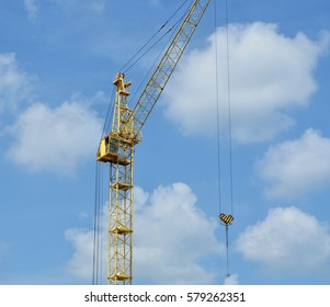 Construction site. Big industrial tower crane with blue sky in background. Modern civil engineering. Construction crane against sky. Close up