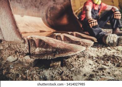 Construction Site Break. Caucasian Worker Taking Short Break and Relax on the Iron Excavator Bucket.