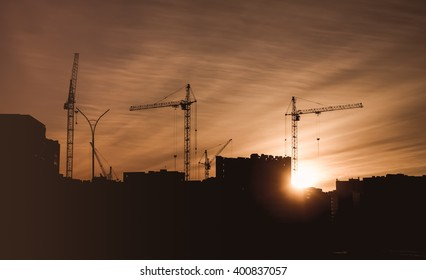 Construction site with the building cranes and houses under construction with a sunset background.