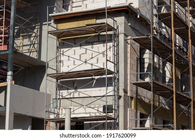 construction site in the construction business, building a new home on the building scaffolding for construction and stucco walls of building