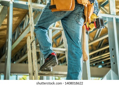 Construction Site Contractor on a Ladder Climbing to Second Floor Keeping Drill Driver in a Hand. Industrial Theme.