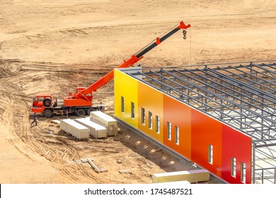 Construction site covered by sand with installed building frame. Builders use mobile crane to mount bright colored sandwich panels on facade of supermarket or mall. City Business Development Project