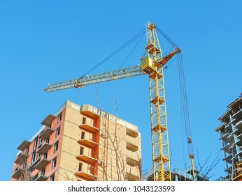 Construction site with crane and building. Crane and building against blue sky.