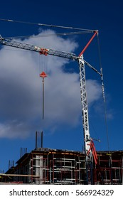 Construction site. Crane and building under construction on the background of sky. (vertical).