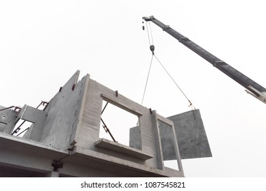 Construction site crane is lifting a precast concrete wall panel to installation building. Isolated on white background.