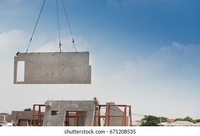 Construction site crane is lifting a precast concrete wall panel to installation building.