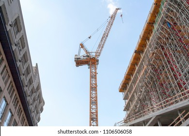 Construction site with crane, scaffold and office building, and a blue sky - Berlin 2018