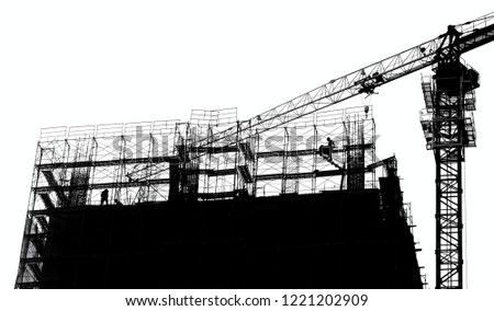 Construction site with crane and scaffolding seen as a silhouette