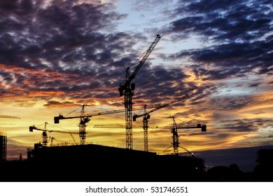 Construction site with crane in silhouette