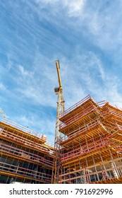 Construction Site with Crane under a Blue Cloudy Sky