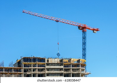 Construction site. Construction cranes and high-rise building under construction against blue sky.