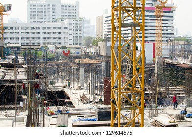 Construction site with  cranes and many workers - all logos are removed