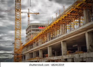 Construction site. Construction cranes, monolithic concrete walls, formwork for concrete. The concept of construction.