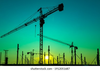 Construction site with cranes on orange sunset, sunrise sky background. Steel frame architect  structure, structural steel beam build large buildings at construction site . construction machinery.