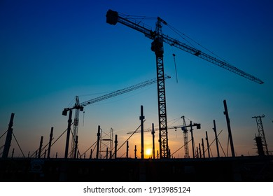 Construction site with cranes on orange sunset, sunrise sky background. Steel frame structure, structural steel beam build large buildings at construction site . construction machinery.