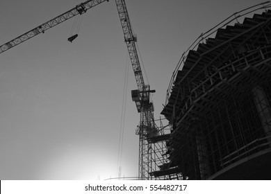 Construction site with cranes on sky background black and white