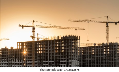 Construction site with cranes at orane yellow sunset. Working with installation metal.
