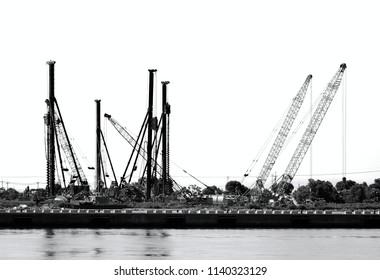 A construction site with drilling rigs and cranes seen in silhouette