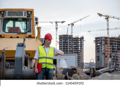 Construction site  engineer stands next to a bulldozer in front of the construction site, looking at the time on his watch .