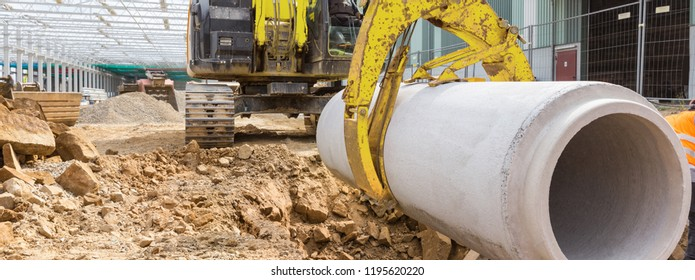 construction site excavator with a concrete pipe