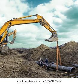 Baustelle, Bagger mit Metallrohr