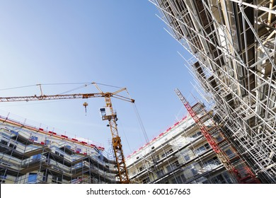 construction site in extreme wide perspective, cranes and scaffoldings