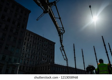Construction site with a group of workers on a scaffold, a concrete pump casting foundation and a crane with its hook against the bright sun.