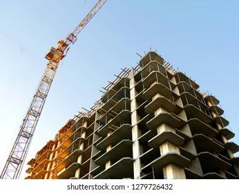 Construction site. High-rise multi-storey building under construction. Tower crane near building.