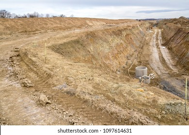 construction site including a big trench with lots of earth and loam