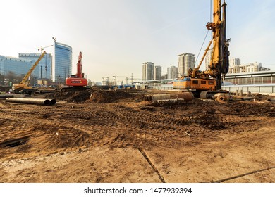 construction site at initial stage of new building. preparation of the ground with drilling rig, excavators and trucks awaiting loading of soil for transportation. Moscow 2018