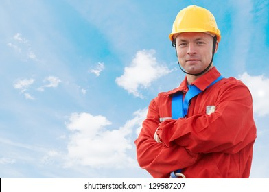 Construction site manager worker in uniform and safety protective equipment over blue sky