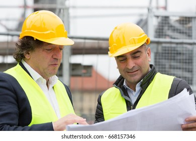 Construction site managers showing and explaining blueprints