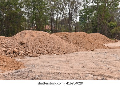 Construction site mounds of dirt and rock. Red orange brown rust color soil