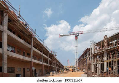 Construction site of multi-story building, view towards scaffolding and heavy equipment.