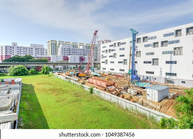 Construction site near completed HDB complex at Eunos, Singapore. Foundation, ground works in progress with heavy equipment machinery, pile driver, building material, scaffolding, fence