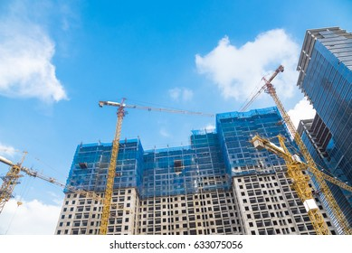 Construction site next to modern office, residential building. Working crane and safety net with cloud blue sky in Hanoi, Vietnam. Green grid prevent objects falling from height. Industrial background