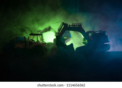 Construction site on a city street. A yellow digger excavator parked during the night on a construction site. Industrial concept table decoration on dark foggy toned background. Selective focus