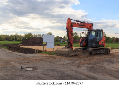 Construction site for one family house filled with sand, empty sign with copy space and digger in building area after earthworks, Germany