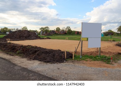 Construction site for one family house filled with sand and empty sign with copy space in building area after earthworks, Germany
