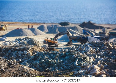 Construction site, process of new road construction with heavy vehicle at building work, heavy excavator and bulldozer unloading road metal during road work