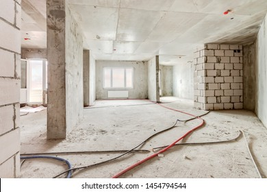 Construction site of residential apartment building interior in progress with windows and white brick wall