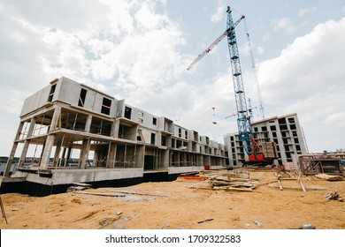 construction site of residential buildings with cranes in sunny weather with blue sky