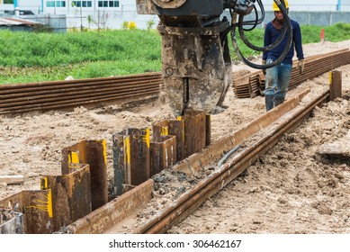 Construction site. Retaining wall steel sheet pile driving machine work control  in construction site