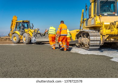 Construction site of road, building or airport with construction machinery (truck, bulldozer, excavator) and construction workers or engineers