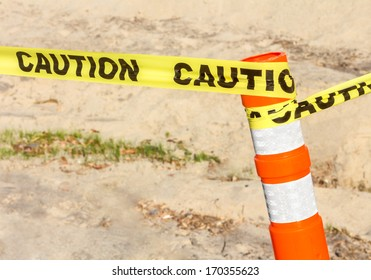 """Construction site sign. Bright yellow ribbon with word """"caution"""" tied to plastic orange post with reflective white tape. Sandy, blurred background. Horizontal photo."""
